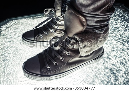 Warm sneakers, sporty shoes standing on cracked glass, cold tonal correction, retro style dark contrast photo filter - stock photo