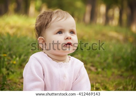 Warm spring time in the park. Little blond caucasian girl sitting in the green grass. Girl thoughtfully looking into the distance - stock photo