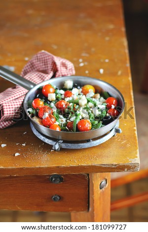 Warm summer salad with roasted cherry tomatoes, blanched french green beans. crumbled feta cheese, clack olives and crispy croutons in a pan for healthy lunch - stock photo