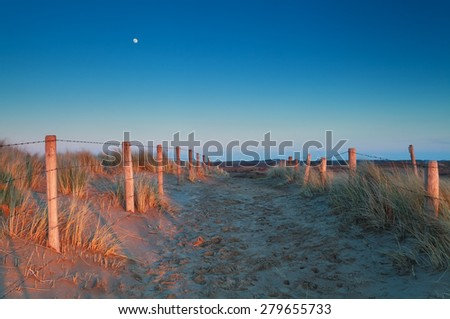 warm sunset light and moon over sand path in dunes - stock photo