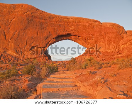 Warm  sunset light on stairs to North Window Arch in Arches National Park. - stock photo