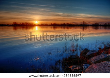 Warm sunset with the outline of trees on the horizon - stock photo