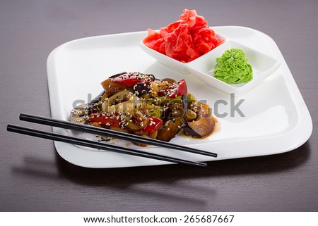 Warm thai salad on white plate over black background - stock photo