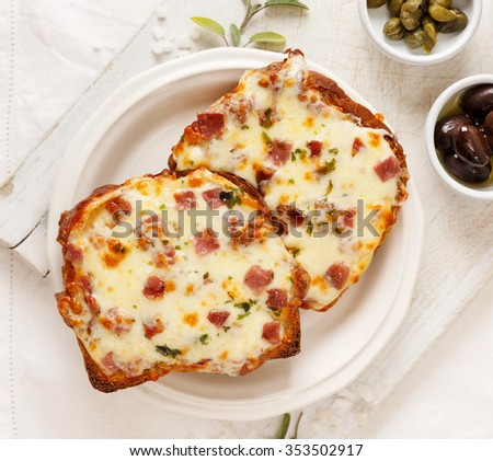 Warm toast with cheese and chopped salami on the white board - stock photo