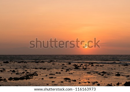 Warm tropical sunset over Agung volcano, the highest mountaint on Bali island, Indonesia with sea and stones on front - stock photo