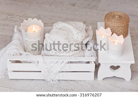 Warm white wool sweaters on white wood stool with candles and tea - stock photo
