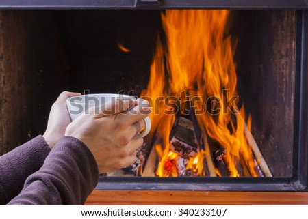 warming hands at fireplace with coffee and tea - stock photo