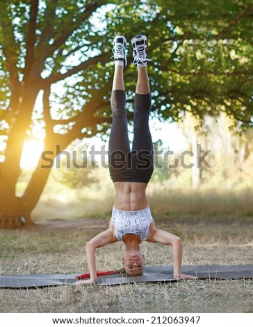 Warming-up. Beautiful young caucasian woman in fitness wear doing exercises in a park - stock photo