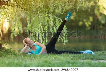 Warming-up. Beautiful young caucasian woman in fitness wear doing pres exercises in a park at the morning - stock photo