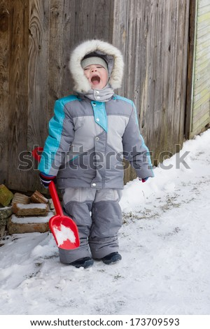 warmly dressed in overalls boy playing outdoors in snowy winter - stock photo