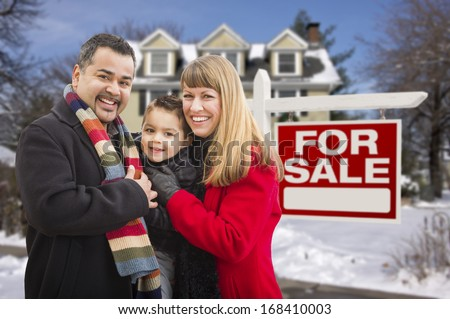 Warmly Dressed Young Mixed Race Family in Front of Home For Sale Real Estate Sign and House with Snow On The Ground. - stock photo