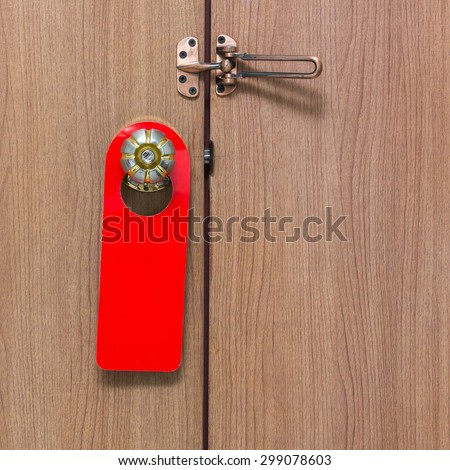 Warning Do Not Disturb sign hanging on the door knob red. - stock photo