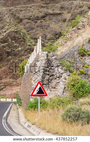 Warning road sign, beware of falling rocks, protection barrier - stock photo