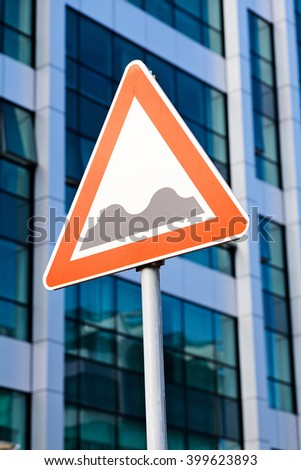 Warning road sign on a pole: bumpy road; business building in background - stock photo