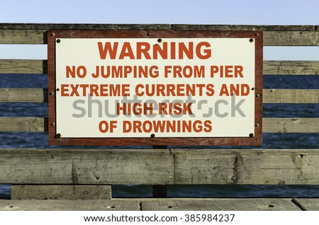 Warning sign at end of pier frequented by fishermen, tourists and other beachgoers in Corpus Christi, Texas, near sunset, for themes of risk awareness, suicide prevention, safety - stock photo