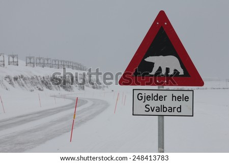 Warning sign in front of polar bears on the road to the airport. In the background the old cable car to the coal industry - stock photo