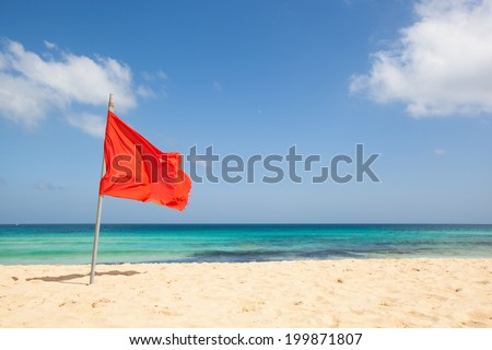 warning sign of a red flag at a beautiful beach with a blue sky and a turquoise sea, Fuerteventura, Canary Islands, Spain, Europe - stock photo