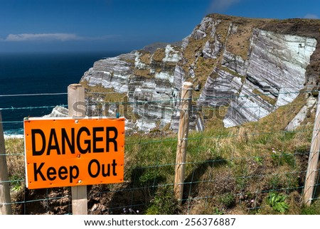 Warning sign on the edge of high cliffs in County Kerry, Republic of Ireland - stock photo