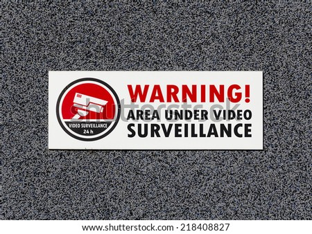 Warning Sign on the Gray Wall Showing Area Under Video Surveillance - stock photo