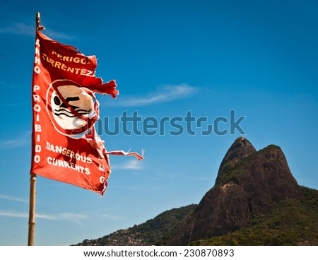 Warning Sign, Ripped Dangerous No Swimming Flag with Mountain Background in Ipanema Beach, Rio de Janeiro, Brazil - stock photo