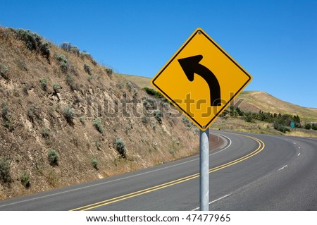 Warning traffic sign on metal pole winding road on background - stock photo