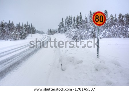 Warning traffic sign on snowy arctic winter road. - stock photo