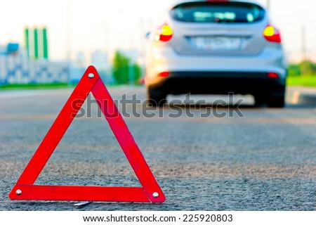 warning triangle on the road and the car moved down to the curb - stock photo
