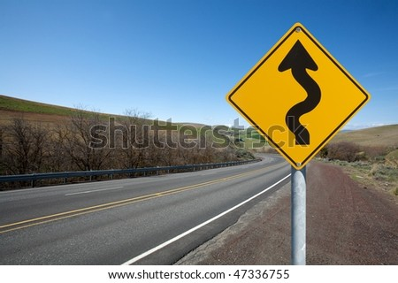 warning winding traffic sign winding road on background - stock photo