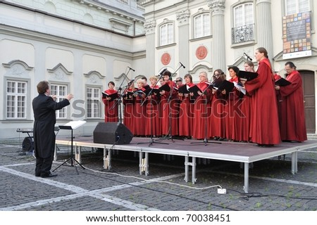 WARSAW - JUNE 28: The Choir of Singing Society from Saska Kepa sing during the concert in the court of the Warsaw Royal Castle on June 28, 2009 in Warsaw, Poland. Artur Backiel conducts the choir. - stock photo