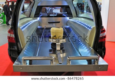"WARSAW - NOVEMBER 20: Burial urn in a hearse at the exhibition of funeral industry ""V Funeral Fair MEMENTO'2010"" on November 20, 2010 in Warsaw, Poland. - stock photo"