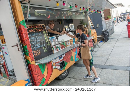 WARSAW, POLAND - AUGUST 2: Woman buys Mexican food during Food Truck festival on August 2, 2014 in Warsaw - stock photo