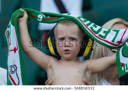 WARSAW, POLAND - AUGUST 09, 2015: Young Legia Warsaw fan during Polish League football match between Legia Warsaw and Wisla Cracow in Warsaw. legia is the most popular football club in Warsaw. - stock photo