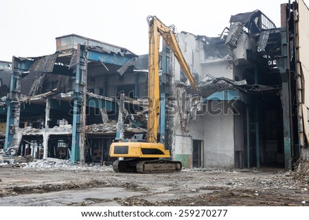 Warsaw, Poland - Feb 2 , 2015: Bulldozer crushing the building at construction site - stock photo