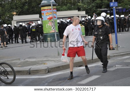 WARSAW, POLAND - JUNE 12, 2012 - Poland soccer fan is moved by riot police, protecting Russian fans marching to the stadium, during the Euro 2012 soccer championship, match between Poland and Russia. - stock photo