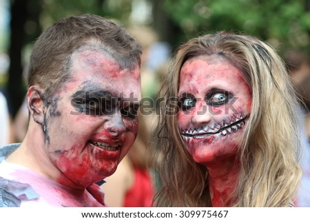 WARSAW, POLAND - JUNE 27, 2015: Unknown people dressed as a zombie parades on a street during a zombie walk. A zombie walk is an organized public gathering of people who dress up in zombie costumes. - stock photo