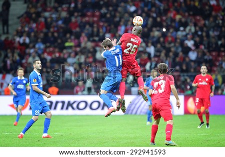 WARSAW, POLAND - MAY 27, 2015: Yevhen Seleznyov of FC Dnipro (L) fights for a ball with Stephane Mbia of FC Sevilla during their UEFA Europa League Final game at Warsaw National Stadium - stock photo