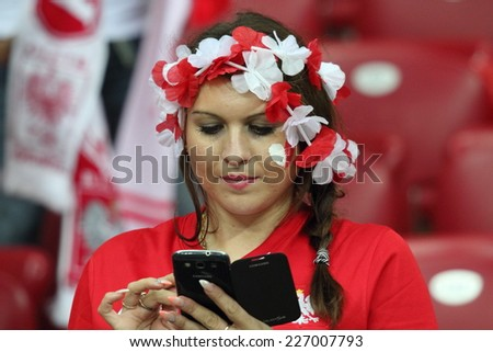 WARSAW, POLAND - OCTOBER 11, 2014: Young unidentified fan of the Polish national football team writes a text message during the UEFA EURO 2016 qualifying match of Poland vs. Germany - stock photo