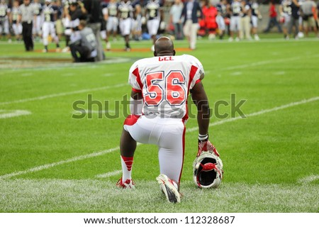 WARSAW, POLAND - SEPTEMBER 1: American football player, US team member Mike Gee (DL/LB) kneels down on the field before the game during Euro-American Challenge match on September 1, 2012 in Warsaw. - stock photo