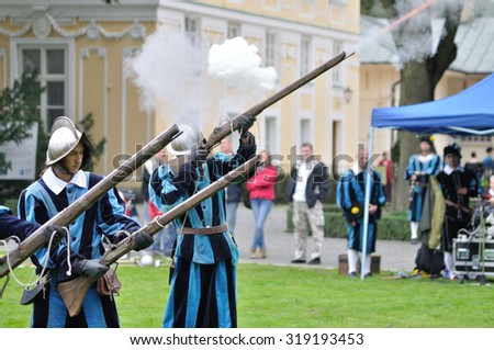 WARSAW, POLAND - SEPTEMBER 11, 2010: Musketeers of the Brotherhood of Knights Nowa Deba show firing musket rifle, during of the Wilanow Days event. - stock photo