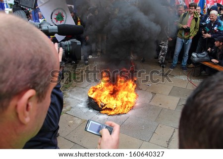 WARSAW, POLAND - SEPTEMBER 11: Unidentified protesters watch burning tires in the street during anti government Solidarity demonstration on September 11, 2013 in Warsaw, Poland. - stock photo
