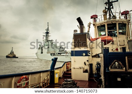 Warship being tugged into a dock - stock photo