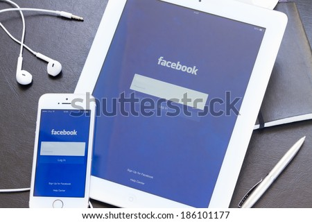 WARSZAWA, POLAND - APRIL 01, 2014: Facebook app on screen of Ipad and Iphone 5s. Facebook is the largest social network in the world. It was founded in 2004 by Mark Zuckerberg and his roommates. - stock photo