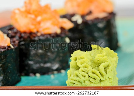 Wasabi with baked sushi rolls made from black rice and salmon, served on turquoise plate. Shallow depth of field. Focus on the wasabi. - stock photo