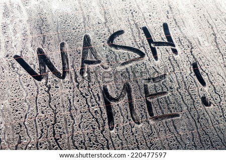 Wash Me Words on a Dirty Rear Car Window - stock photo