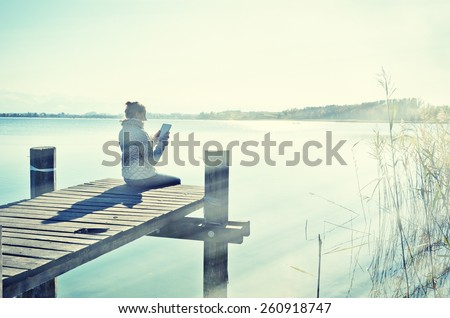 Washed out photo look. Girl reading from a tablet on the wooden jetty against a lake. Switzerland - stock photo