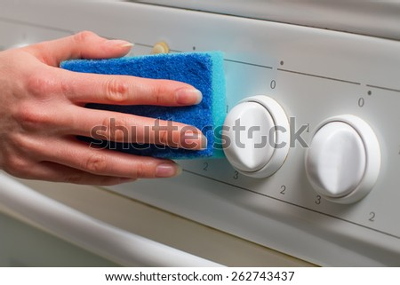 Washing electric stove blue sponge at home. - stock photo