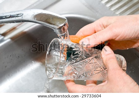 Washing glass in the kitchen - stock photo