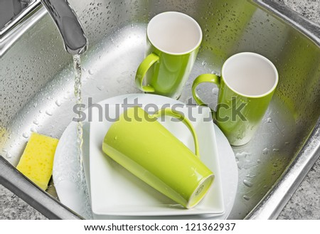 Washing green cups and white plates in the kitchen sink. Water running from the tap. - stock photo