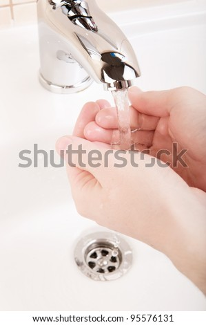 Washing hands closeup with modern metal faucet - stock photo