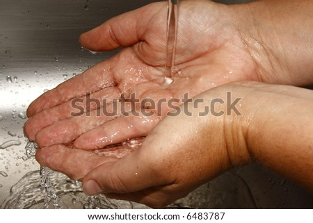 washing hands under running water in a aluminuim basin - stock photo